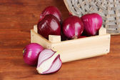 Purple onion in wooden box on wooden background — Stock Photo