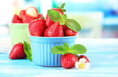 Reife süße erdbeeren in schalen auf blau holztisch — Stockfoto