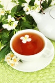 Cup of tea with jasmine, on wicker mat background — Stock Photo