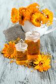 Bouteilles de médicament et de fleurs de calendula sur fond en bois — Photo