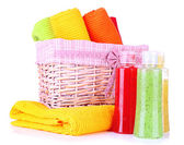 Colorful towels in basket and cosmetics bottles, isolated on white — Stock Photo