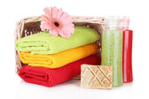 Colorful towels in basket cosmetics bottles and soap, isolated on white — Stock Photo