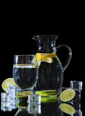 Glass pitcher of water and glass isolated on black — Stock Photo