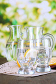 Glass pitchers of water and glasses on wooden table on natural background — Stock Photo