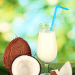 Glass of coconut milk and coconuts on green background close-up — Stock Photo #27784527