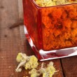 Dried herb in glass container on wooden table close-up — Stock Photo #27785973