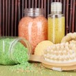 Cleanser, brush and cosmetics for shower on table on bamboo background — Stock Photo