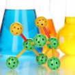 Molecule model and test tubes with colorful liquids close up — Zdjęcie stockowe