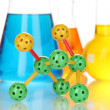 Molecule model and test tubes with colorful liquids close up — Stockfoto