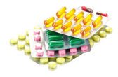 Capsules and pills packed in blisters, isolated on white — Stock Photo