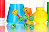 Molecule model and test tubes with colorful liquids close up — Stock Photo
