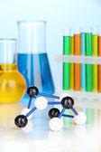 Molekül-modell und reagenzgläser mit bunten flüssigkeiten auf blauem hintergrund — Stockfoto