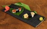 Gustosi maki sushi - roll sul tappetino su sfondo marrone — Foto Stock