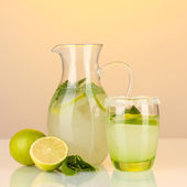 Lemonade in pitcher and glass on yellow background — Stock Photo