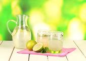 Citrus limonade in werper en bril op houten tafel op natuurlijke achtergrond — Stockfoto