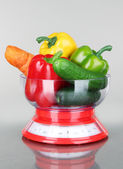 Fresh vegetables in scales on gray background — Stock Photo