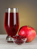 Glass of fresh garnet juice on table on gray background — Stock Photo