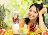 Girl with fresh fruits on natural background — Stock Photo