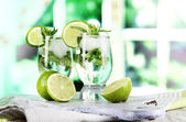 Glasses of cocktail with ice on board on napkin on wooden table on window background — Foto Stock
