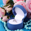 Rose and engagement ring on blue cloth — Stock Photo #27815275