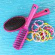 Scrunchies, hairbrush and hair - clip on blue background — Stock Photo #27817317