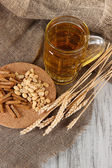 Beer in glass, crackers and nuts on bagging on wooden table — Stock Photo