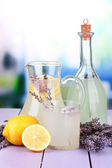 Lavender lemonade in glass bottle and jug, on violet wooden table, on bright background — Stock Photo