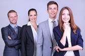 Business team standing in row on grey background — 图库照片