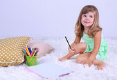 Little cute girl sitting on carpet and drawing pictures, on gray background — Stock Photo