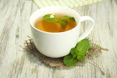 Cup of herbal tea with fresh mint on wooden table — Stock Photo