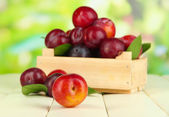 Ripe plums in wooden box on wooden table on natural background — Stock Photo