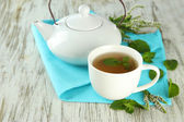 Teapot and cup of herbal tea with fresh mint flowers on wooden table — Stock Photo