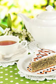 Delicious poppy seed cake with cup of tea on table on bright background — Stock Photo