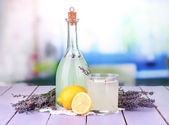 Lavender lemonade,in glass bottle, on violet wooden table, on bright background — Stock Photo