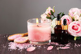 Beautiful pink candle with flowers and towel on bamboo mat — Stock Photo