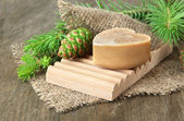 Hand-made soap and green pine cones on wooden background — Stock Photo