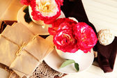 Roses in cups on napkins on wooden background — Stock Photo