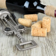 Corkscrew with wine corks and bottle of wine on wooden table close-up — Stock Photo #27842869