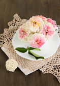 Roses in cup on napkins on wooden background — Stock Photo