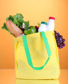 Eco bag with shopping on orange background — Stok fotoğraf
