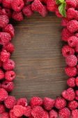 Ripe sweet raspberries on wooden background — Stock Photo