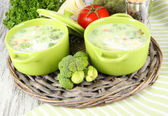 Cabbage soup in plates on braided tray on napkin on wooden table — Stock Photo