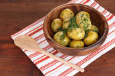 Boiled potatoes on wooden bowl on napkin on wooden table — Stock Photo