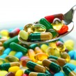 Colorful capsules and pills on plate with spoon, close up — Stock Photo #27892771