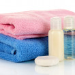 Hotel cosmetic bottles with towel isolated on white — Stock Photo