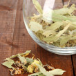 Dried herb in glass container on wooden table close-up — Stock Photo #27894807