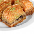 Sweet baklava on plate isolated on white — Stockfoto