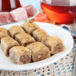 Sweet baklava on plate with tea on table — Stockfoto