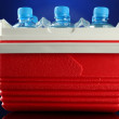 Traveling refrigerator with bottles of water and ice cubes, on blue background — Stock Photo #27896219