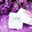 Beautiful box with wedding ring on purple background — Stock Photo